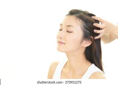 Woman in spa salon receives head massage