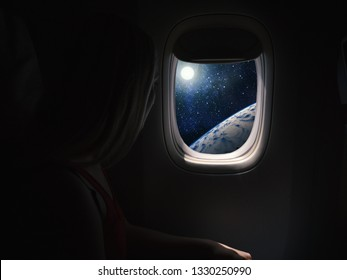 Woman in spaceship looks out the porthole. Commercial space travel concept.