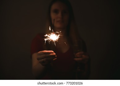 Woman with sparkler on dark background. Celebrating new year with sparkler