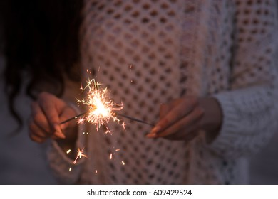 Woman with sparklers near the sea