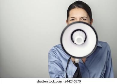 Woman speaking over a megaphone as she makes a public address, participates in a protest or organises a rally or promotion, over grey with copy space to the side