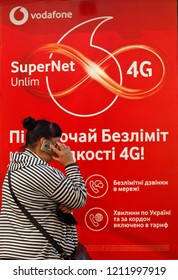 A woman speaks on a phone next to advertising with logo SuperNet Unlim 4G of Vodafone mobile operator placed on the kiosk in a street in Kiev, Ukraine, on 18 October 2018.