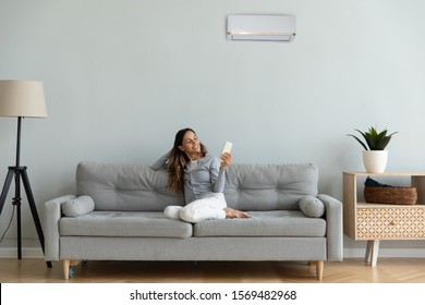 Woman spend time at home seated on sofa holding remote control manages degrees uses air conditioner enjoy air-conditioned contemporary flat, reduces heat or cold weather to comfortable temperature