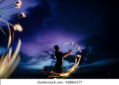 Woman is spinning fire. Awesome moment with beautiful sunset.