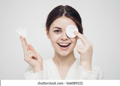woman with a sponge blue background cotton pad problem skin