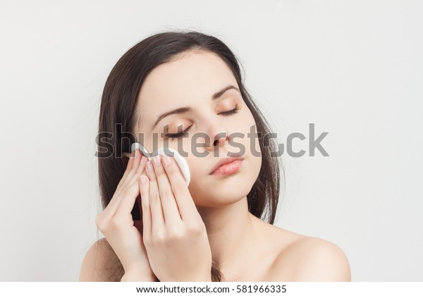 woman with a sponge blue background cotton pad problem skin .