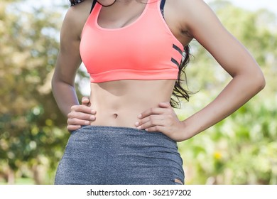 Woman in sport bra checking on her belly - fear of being fat