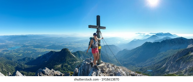 A woman in a sport bra standing under a metal cross with a panoramic view on the Alps from the top of Mittagskogel in Austrian Alps. Clear and sunny day. A bit of haze in the valley. Outdoor activity