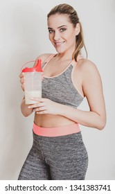 Woman in sport clothes holding protein cocktail on white background.