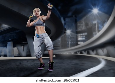 woman in sport dress at piloxing exercise on the night street