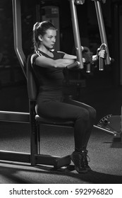 Woman at the sport gym doing arms exercises on a machine. Dark sport club. Black and white.