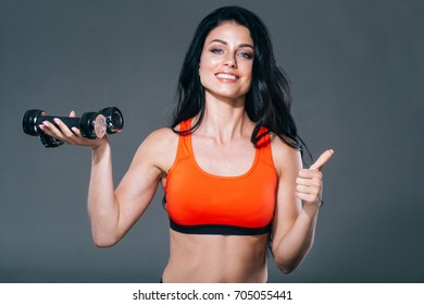 Woman sport studio portrait. Woman with dumbbells over gray background.