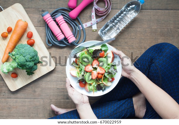 Woman in sport wear holding a dish of fresh salad with strawberries and kiwi, Healthy lifestyle, Woman eating healthy food