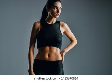 woman in sport wear on gray background holds hand on belt cropped view