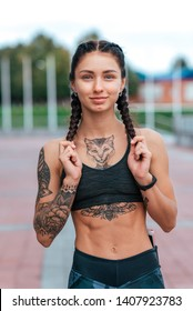 Woman sports coach, summer city, happy smiling fitness workout. Motivation strength mind and thoughts. Tattoo cats chest. Smart bracelet, watch. Hair braids. Beautiful girl in morning on run.