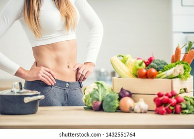 Woman with sports figure home kitchen with wooden box full of organic vegetable.