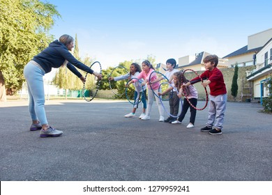 Woman as a sports teacher shows children an exercise with tires in physical education
