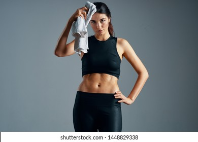 Woman in sportswear belly and towels in hand