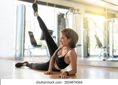 woman in sportswear doing leg workout exercise, side leg lift raise at gym.