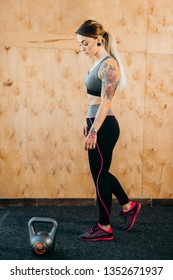 Woman in sportswear doing workout with kettle bell at the gym