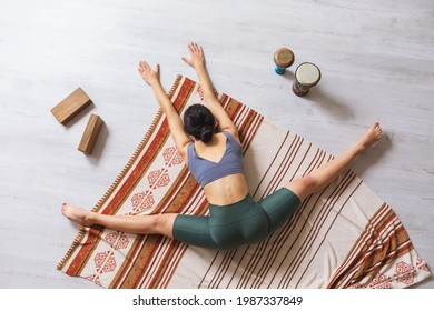 A woman in sportswear, doing yoga, performs a samokanasana exercise while sitting on a blanket, a transverse split with the body tilted forward.
