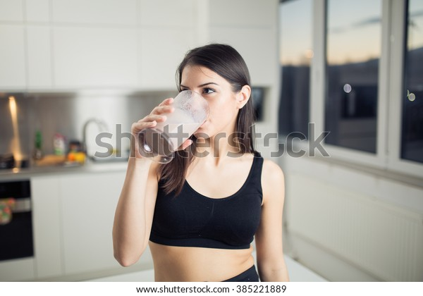 Woman in sportswear  drinking sweet banana chocolate protein powder milkshake smoothie.Drinking protein after workout.Whey,banana and low fat milk sport nutrition diet after gym.Healthy lifestyle