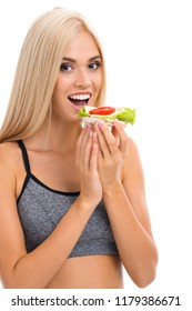 Woman in sportswear eating vegetarian sandwich, isolated on white background. Young sporty blond model at studio shot. Health, beauty and dieting concept.