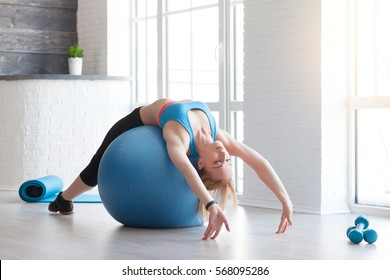 Woman in sportswear exercising her abs on a blue Pilates ball of fitball close up at home. Fitness concept