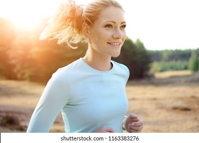 Woman in sportswear jogging, running and training outdoors on a sunny day in summer