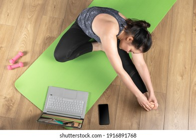 Woman in sportswear make remote yoga exercise yoga class. woman do fitness workout, stretching exercises using laptop via videocall. Top view. watching online yoga class on laptop computer