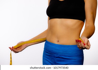 Woman In SportsWear With Measuring Tape On A White Background