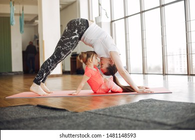 Woman in a sportswear. Mother with little daughter. Family are engaged in gymnastics in a gym