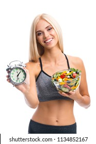 Woman in sportswear with plate of salad and alarm clock, isolated over white background. Young sporty blond model at studio shot. Healthy nutrition and time for dieting and fitness concept.