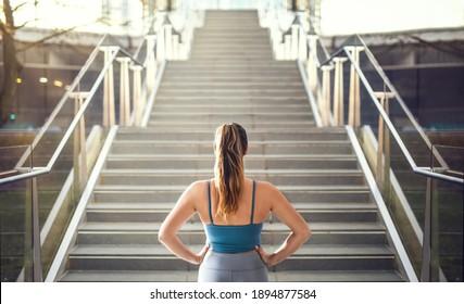 Woman in sportswear preparing for stair run.