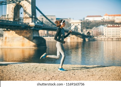 Woman in sportswear running on Danube river promenade in Budapest, Hungary