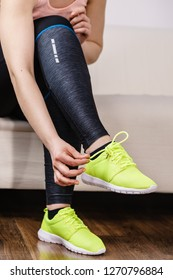 Woman in sportswear sitting on sofa indoor getting ready for exercises. Tying up shoes