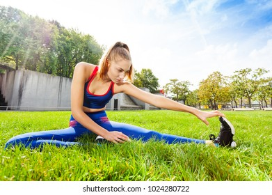 Woman in sportswear stretching legs before workout