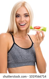 Woman in sportswear with vegetarian sandwich, isolated over white background. Young sporty blond model at studio shot. Health, beauty and dieting concept.