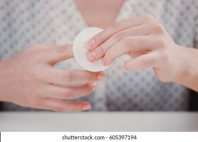 Woman in spotted blouse is cleaning nail polish with the cotton pad
