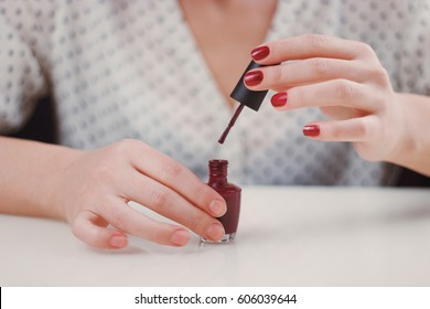 Woman in spotted blouse is painting her nails with red nail polish