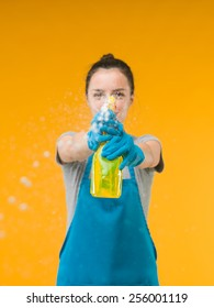 woman spraying cleaning detergent on surface in front of her