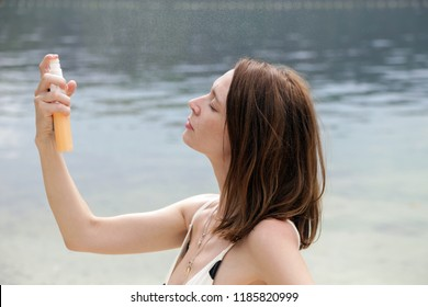 Woman spraying facial mist on her face at the beach, skin care concept
