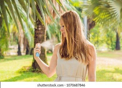 Woman spraying insect repellent on skin outdoor