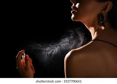 Woman spraying luxury perfume on black background, closeup