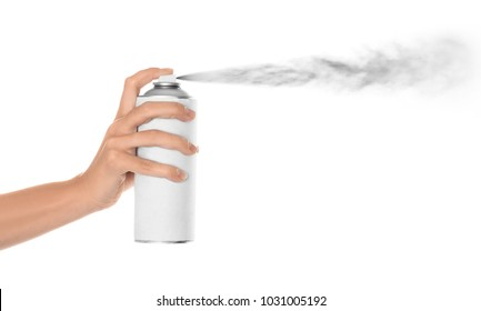 Woman spraying paint from can on white background