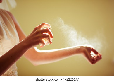 Woman sprays perfume over her delicate wirst
