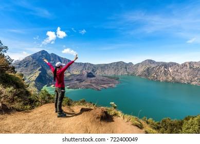 Woman spreading hand, enjoy and happy with active volcano Baru Jari, Lake Segara Anak and summit of Rinjani mountain view after finished climbing at Rinjani mountain, Lombok, Indonesia.