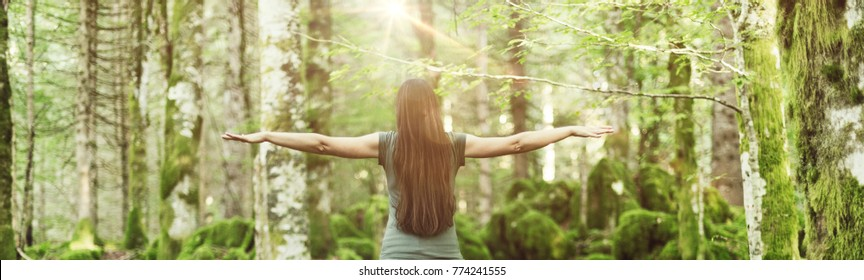 Woman spreading her arms in the forest back view: balance, spirituality and nature concept