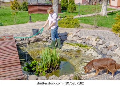 Woman in the spring cleans the artificial pond near her house.