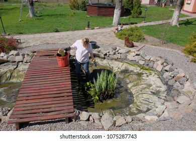 A woman in the spring cleans an artificial pond in the yard of her house.